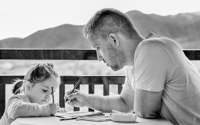 Padre hija haciendo los deberes en la terraza