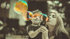 Madre e hijo jugando con un soplador de burbujas - COVID19 y régimen de visitas