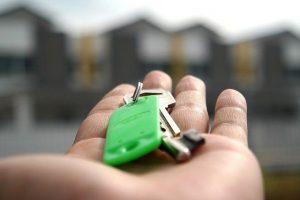 palma de la mano con unas llaves y una fila de casas de fondo